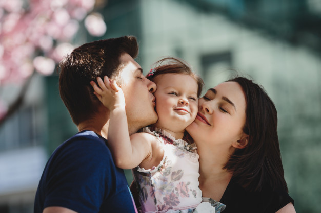 happy young parents with little daughter stand blooming pink tree outside