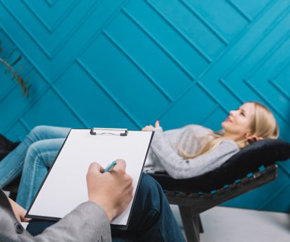 psychologist listening her female patient lying couch writing down notes   e